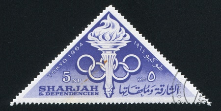 SHARJAH AND DEPENDENCIES - CIRCA 1964: stamp printed by Sharjah and Dependencies, shows Olympic rings and Flame, circa 1964 Stock Photo - 17145547