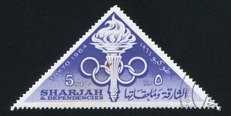 dependencies: SHARJAH AND DEPENDENCIES - CIRCA 1964: stamp printed by Sharjah and Dependencies, shows Olympic rings and Flame, circa 1964 Editorial