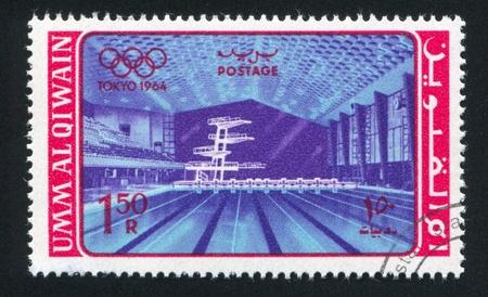piscina olimpica: Umm al-Quwain - CIRCA 1964: sello impreso por Umm al-Quwain, muestra piscina olímpica, alrededor de 1964