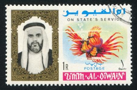 UMM AL-QUWAIN - CIRCA 1972: stamp printed by Umm al-Quwain, shows Sheikh and Fish, circa 1972 Stock Photo - 17145837