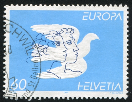 SWITZERLAND - CIRCA 1995: stamp printed by Switzerland, shows Dove and faces, circa 1995 Stock Photo - 17464386