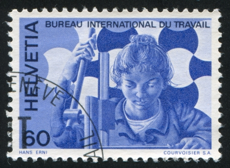 SWITZERLAND - CIRCA 1975: stamp printed by Switzerland, shows Woman at drilling machine, circa 1975 Stock Photo - 18114199