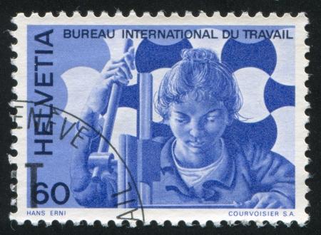 SWITZERLAND - CIRCA 1975: stamp printed by Switzerland, shows Woman at drilling machine, circa 1975 Stock Photo - 18114199