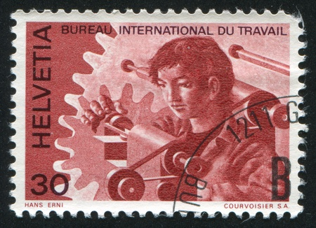 machinetool: SWITZERLAND - CIRCA 1975: stamp printed by Switzerland, shows Young man at lathe and cogwheels, circa 1975 Editorial