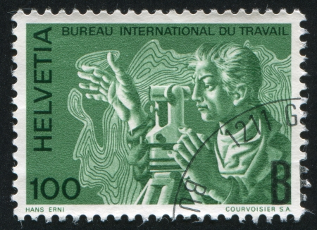 SWITZERLAND - CIRCA 1983: stamp printed by Switzerland, shows Surveyor with theodolite and topographical map, circa 1983 Stock Photo - 18114443