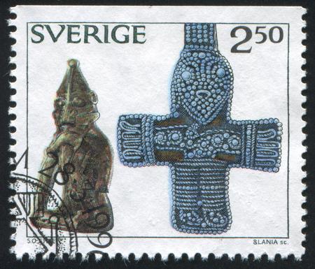 fertility emblem: SWEDEN - CIRCA 1990: stamp printed by Sweden, shows Bronze statue of pagan fertility god, silver filigree cross, circa 1990
