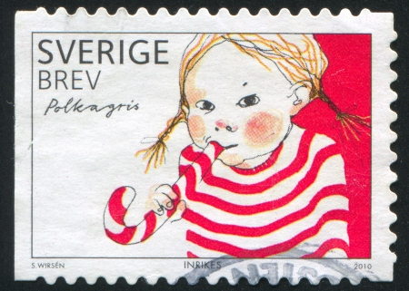 tucker: SWEDEN - CIRCA 2010: stamp printed by Sweden, shows Girl with caramel, circa 2010