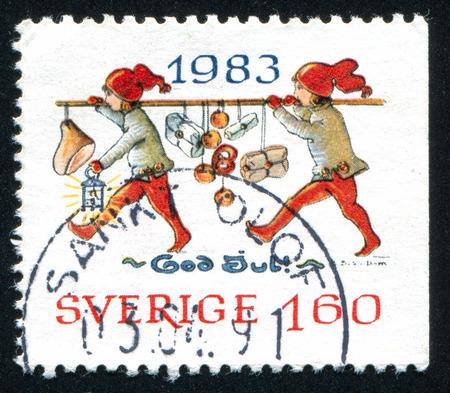 gnomos: SUECIA - CIRCA 1983: sello impreso por Suecia, muestra Gnomos llevar los regalos de Navidad en un poste, alrededor de 1983 Editorial