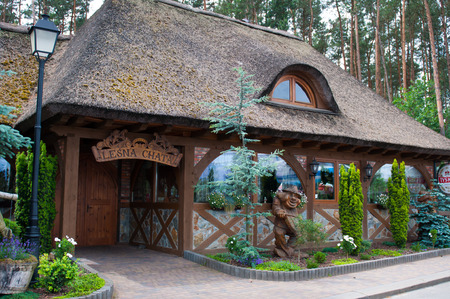 thatched house: Old house with thatched roof in Poland. Wooden sculpture.