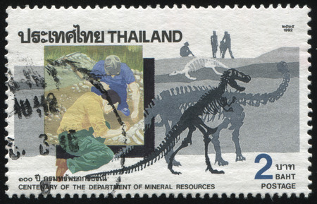 tyrannosaur: RUSSIA KALININGRAD, 31 MAY 2016: stamp printed by Thailand, shows illustration of two archeologists in the field, dedicated to centenary of the department of mineral resources, circa 1992