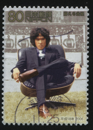 elbow chair: RUSSIA KALININGRAD, 18 MARCH 2016: stamp printed by Japan, shows an asian man sitting in the chair on tribune background, circa 2006