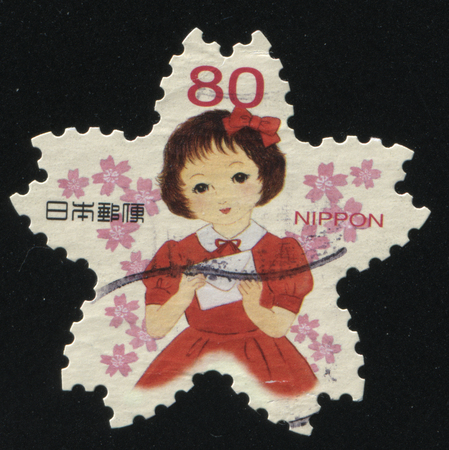RUSSIA KALININGRAD, 19 APRIL 2016: stamp printed by Japan, shows a young girl among the flowers with the letter in her hands, circa 2011