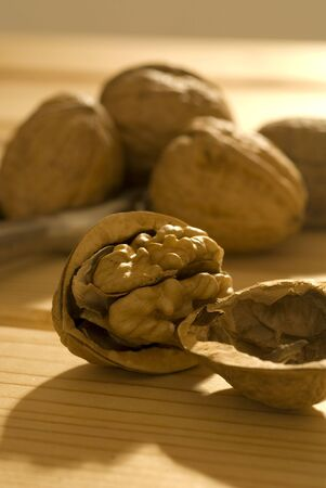 disclose: Group of walnuts on wooden table, in warm morning light.