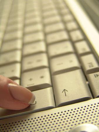 Finger is pressing enter on a laptopo keyboard. Stock Photo - 2119216