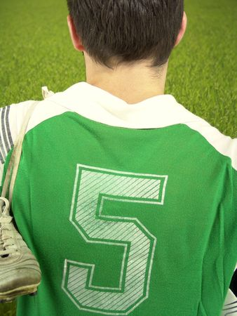Young football player ready to begin a match. In front of him a green lawn, according to colour of his team. A metaphor to all challenges looking to the future. photo