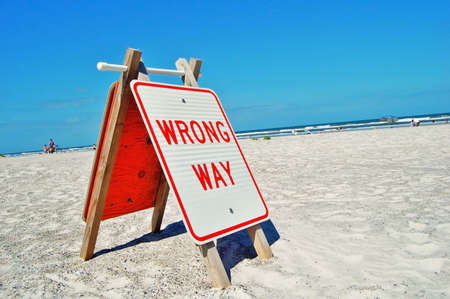wrong way sign on a beach photo