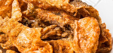 fish skin: Spicy fried fish skin in a white dish.