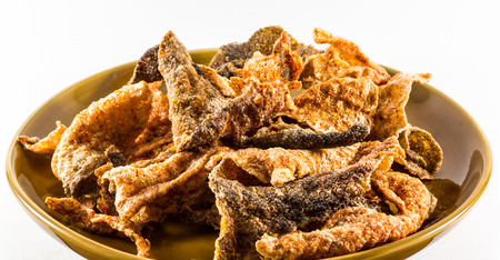 fish skin: Spicy fried fish skin on the plate on a white background. Stock Photo