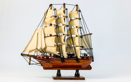 Antique model sailing ship with white background.