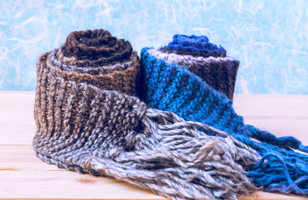 tog: Two roll knitted scarf on wooden and paper background. Stock Photo