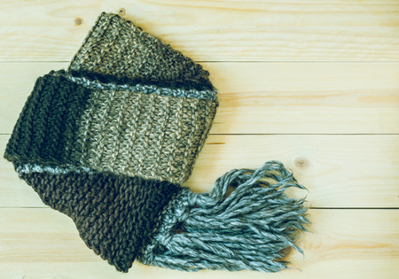 tog: Knitted scarf on wooden background.