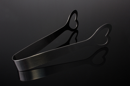 tongs: Stainless steel love heart ice tongs isolated on gray gradient background