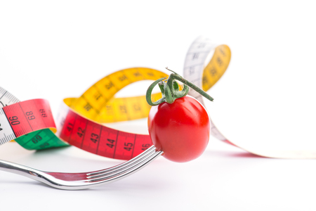 metering: Fork, tomato and metering tape over the white background, isolated Stock Photo