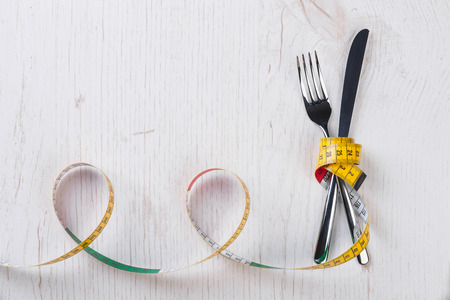 metering: Fork and knife tied with metering tape on the white wooden table