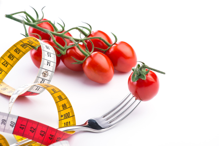 metering: Fork, tomatoes and metering tape over the white background, isolated