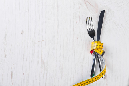 weight loss plan: Fork and knife tied with metering tape on the white wooden table