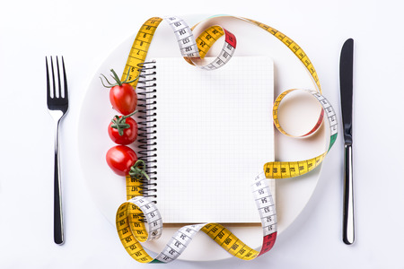metering: Plate, fork, knife, metering tape, tomatoes and notebook on light wooden table