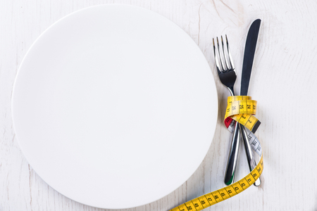 metering: Plate, fork, knife and metering tape on light wooden table