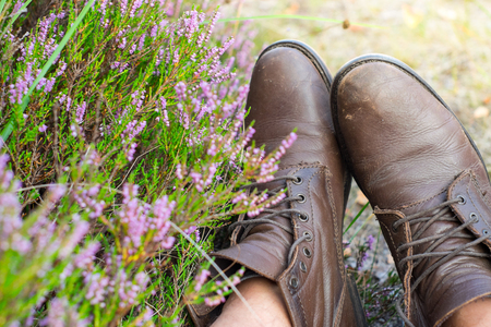 walking boots: A pair of heavy worn brown leather shoes over the countryside background