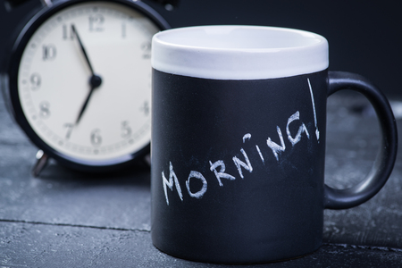 second breakfast: Black tea cup with alarm clock on wooden table