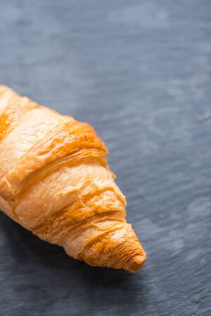 crusty: Tasty and crusty french croissant on a black stone plate in a dayligt