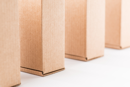 ship order: Brown cardboard boxes standing in a row over the white background Stock Photo