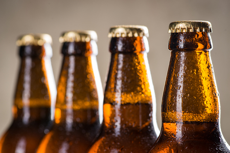 dew cap: Ice cold beer bottles in a row over the grey concrete wall background