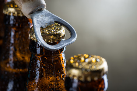 Brown ice cold beer bottles with water drops and old opener Standard-Bild