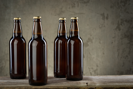 Four ice cold beer bottles in a row over the grey concrete wall background