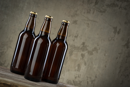 dew cap: Three ice cold beer bottles in a row over the grey concrete wall background