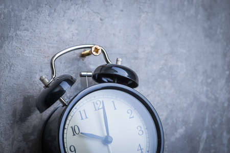 test deadline: Unusual picture of old vintage alarm clock hanging on the grey concrete wall Stock Photo