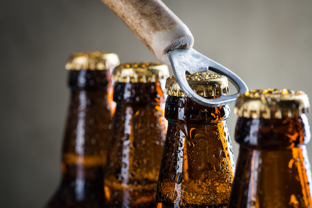 cold drinks: Brown ice cold beer bottles with water drops and old opener Stock Photo