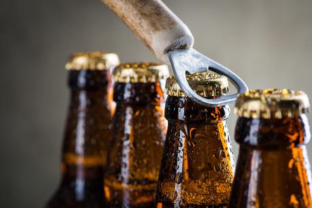 bebidas frias: hielo marrón botellas de cerveza fría con gotas de agua y abridor de edad