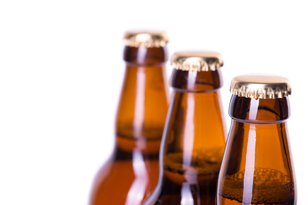 dew cap: Three brown bottles of ice cold beer isolated on white Stock Photo