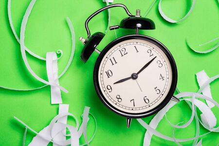 teared: Old vintage alarm clock standing on the green paper surface with pieces of teared paper