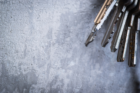 A bunch of old worn keys hanging on the screw on the grey concrete wall Standard-Bild