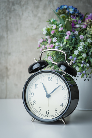 night table: Vintage alarm clock on a night table with flowers Stock Photo