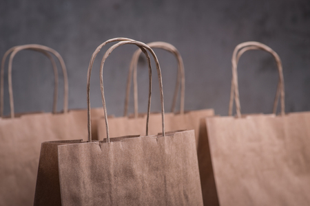 gift bags: Four craft paper bags over the concrete wall background Stock Photo