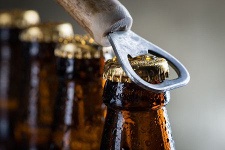 Brown ice cold beer bottles with water drops and old opener Фото со стока