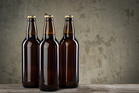 brown bottles: Three ice cold beer bottles in a row over the grey concrete wall background